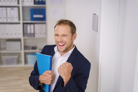clutches: Successful businessman cheering a victory or achievement pumping the air with his fist as he clutches a blue file Stock Photo