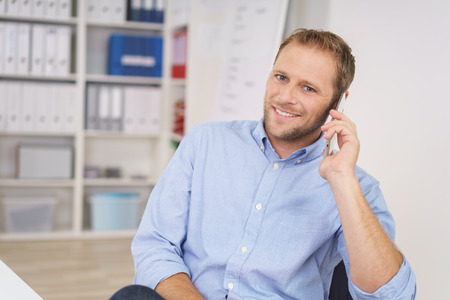 Handsome relaxed young businessman chatting on his mobile at the office smiling at the camera as he listens to the call