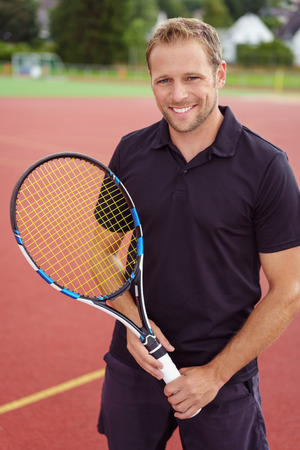 a hobby: Confident happy male tennis player standing on an outdoor all weather court with his racket in his hands smiling at the camera Stock Photo
