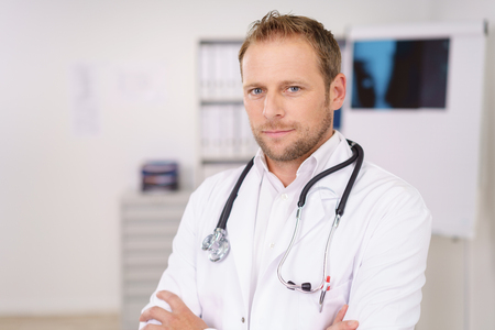 Serious attractive male doctor standing with folded arms in his lan coat looking at the camera with a thoughtful expression Stock Photo