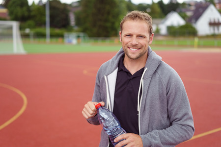 quench: Smiling sporty man holding a bottle of water to quench his thirst as he stands on an outdoor court in a grey hoodie Stock Photo
