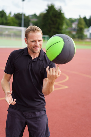 sports track: Skilled sports coach spinning a ball on his finger in a demonstration on a field race track at a sports arena Stock Photo
