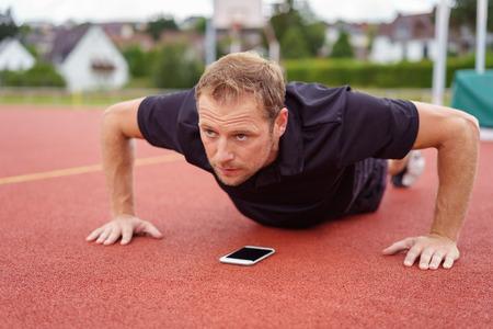 sportsman: Único hombre barbudo serio haciendo push ups sobre teléfono inteligente que está utilizando para un temporizador durante el ejercicio Foto de archivo