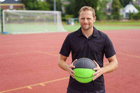 short sleeve: Smiling man in short sleeve shirt holding green and black ball near outdoor goal net