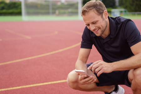 sports field: Athlete or sports trainer checking his mobile phone for messages as he squats on an outdoor race track in a sports arena