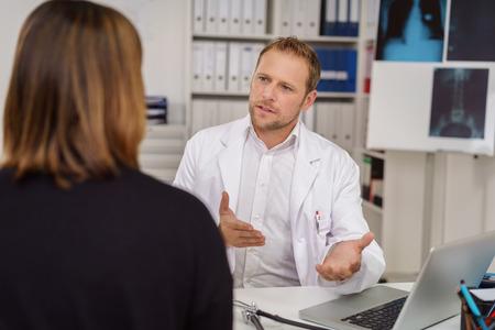 Oprechte mannelijke arts van de arts iets uit te leggen aan een vrouwelijke patiënt met zijn handen gebaren als hij praat