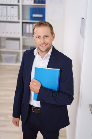 mid thirties: Young businessman standing outside the door of his boss or supervisor with a folder under his arm looking at the camera with a quiet smile , high angle view