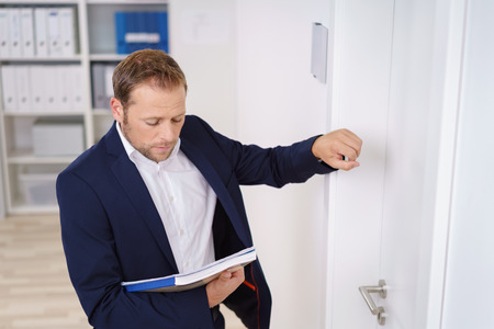 Young businessman knocking on the door of the boss as he stands outside looking down at a folder in his hand Foto de archivo