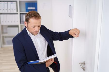 Joven empresario llamando a la puerta del jefe como él se coloca fuera mirando hacia abajo en una carpeta en la mano Foto de archivo - 65439802