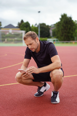 squatting down: Athletic man checking his mobile on an all weather outdoor court in a sports complex squatting down on his haunches reading a text message