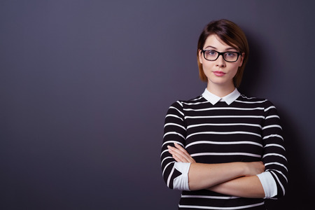 Cute young woman with serious expression and folded arms leaning on wall with copy space