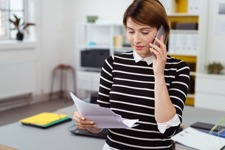 Young businesswoman discussing a document over her mobile phone as she stands in the office Stock Photo