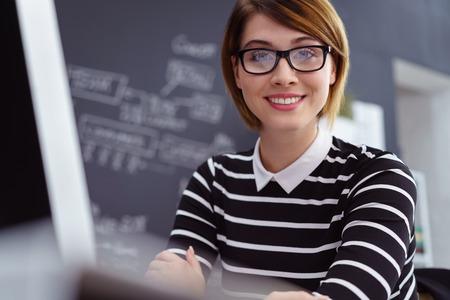 Chiuda in su di bello giovane scienziato informatico sorridente della femmina adulta con le note oscurate sulla lavagna dietro lei Archivio Fotografico