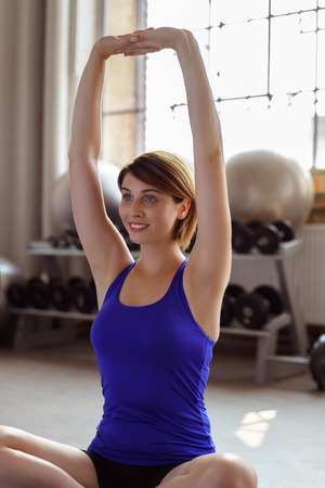 arms above head: Young woman working out on a yoga mat in a gym doing aerobics exercises stretching her arms above her head
