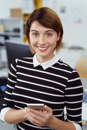 Short haired young woman in black and white striped sweater holding device while standing in office setting Stock Photo