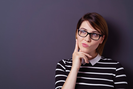 girl glasses: Single young attractive thinking woman with fingers on chin and short hair over dark background