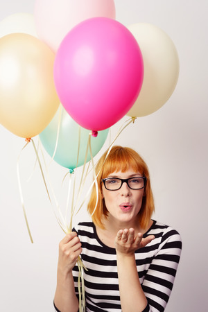 flirty: Flirty young redhead woman blowing a kiss across the palm of her hand as she holds a colorful bunch of party balloons
