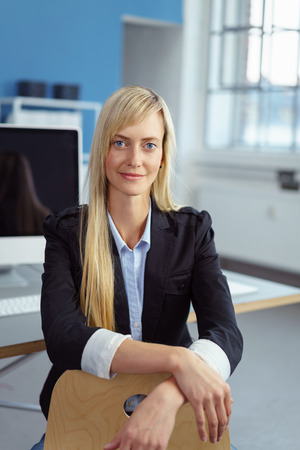 blazer: Friendly relaxed businesswoman in the office leaning her hands on the back of her chair looking at the camera with a smile Stock Photo