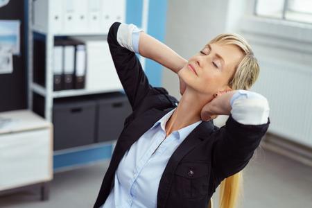 ejercicio: Empresaria joven tensionada desestresante en la oficina reclinándose en su silla con las manos entrelazadas detrás de la cabeza y los ojos cerrados