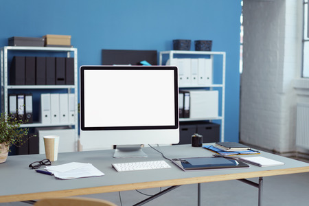 empty office: Neat office workspace with a blank screen desktop computer, tablet, coffee, spectacles and notepads