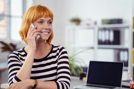 personen: Happy jonge zakenvrouw het maken van een gesprek in het kantoor als ze zit aan haar bureau te luisteren naar het gesprek met een glimlach