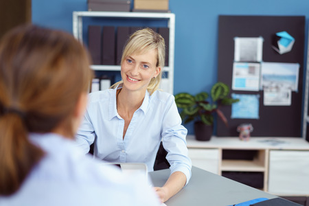 Attractive young woman in a business interview for a job vacancy listening attentively to the female interviewer with a smile, over the shoulder view Foto de archivo