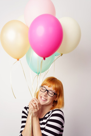 Happy young redhead woman in love holding onto a bunch of colorful party balloons with a beaming smile and her eyes closed tenderly in bliss and delight