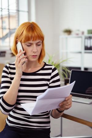 affari Preoccupato discutendo un documento al telefono come lei si trova in ufficio tenendo i documenti in mano