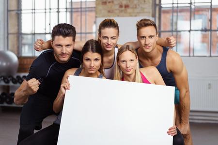 Twee mooie en ernstige vrouwen die lege affiche in gymnastiek met drie vrienden achter hen houden