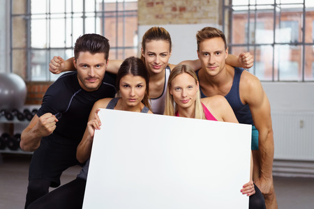 sports hall: Two beautiful and serious women holding blank poster in gym with three friends behind them Stock Photo