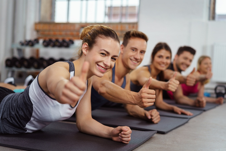 Group of five cheerful adults laying on mats while doing thumb up gesture in fitness room with weight rack behind them