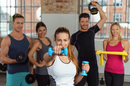 companions: Fit woman with excited expression showing off dumbbells and pointing while her companions are holding kettle bells and resistance bands