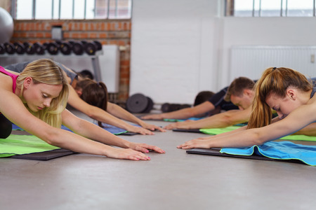 joga: Group doing joga on floor of exercise gym while side by side on yoga mats Stock Photo