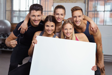 sports hall: Two smiling women holding blank poster in gym with three happy friends behind them Stock Photo