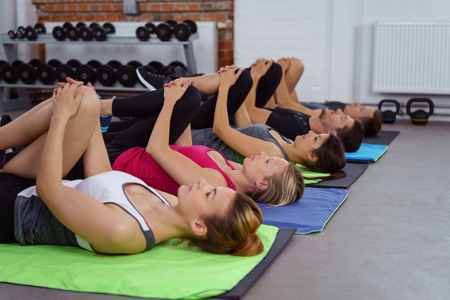 backs: Group of five calm adults on their backs doing muscle stretching cool down exercises in gym