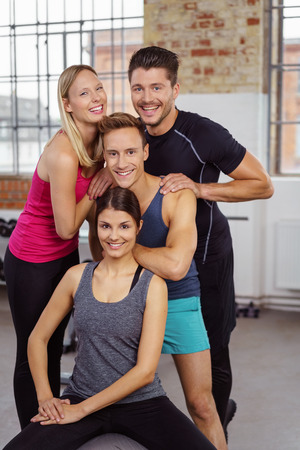 sports hall: Four young adult and attractive happy male and female friends together at gym with happy expressions