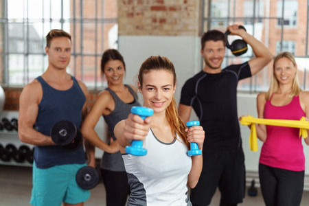 companions: Beautiful fit woman showing off dumbbells while her companions are holding kettle bells and resistance bands Stock Photo
