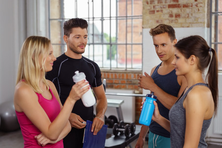 sip: Four attractive men and women chatting at gym while taking a break to sip water from bottles