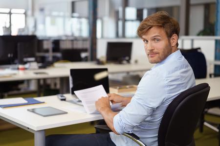 いぶかしげな気な表情でカメラを振り返る彼の椅子を回してドキュメントを読むビジネスマン
