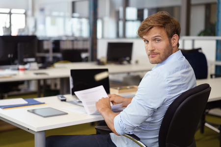 Businessman reading a document turning in his chair to look back at the camera with a quizzical distracted expression Standard-Bild