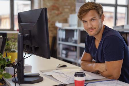 Handsome ghignante uomo caucasico con le braccia piegate a una scrivania di fronte a schermo del computer a schermo piatto in ufficio