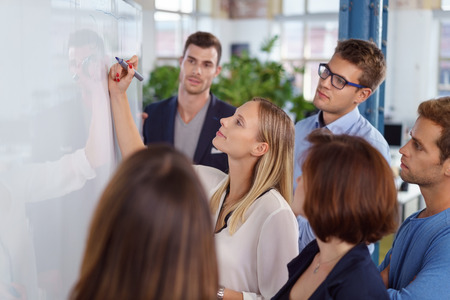 Confident blond woman writing on blank white board with fellow young adult workers standing around smiling Stockfoto