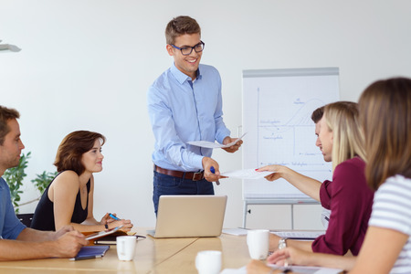 presenting: Businessman doing in house training with colleagues smiling as he hands out notes to one of the people seated around the conference table