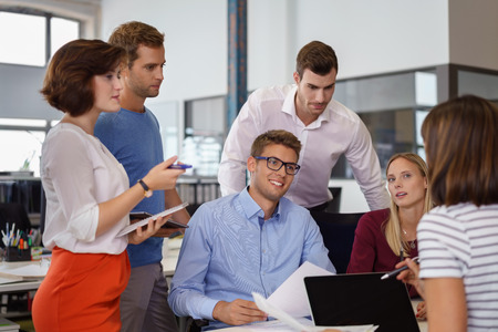 long sleeve shirt: Happy attractive man in blue long sleeve shirt and eyeglasses with workers in office during meeting Stock Photo