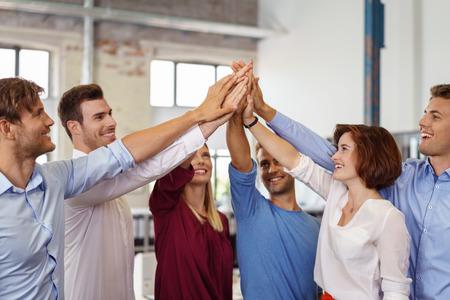 やる気のある若いビジネス チーム約束サポート幸せの熱狂的な笑顔でピラミッドに手を上げて