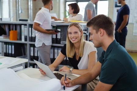 조직: 그들은 바쁜 개방형 사무실에서 테이블에 노트북 컴퓨터를 공유하는 남성 동료와 함께 작동하는 젊은 사업가 웃