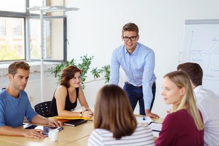Le chef d'équipe avec sa jeune équipe de gens d'affaires divers assis autour d'une table de conférence à une réunion ayant une discussion sérieuse Banque d'images