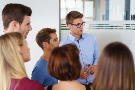 office cubicle: Group of Caucasian workers standing around each other in small office glass cubicle setting