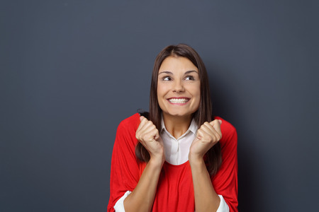 excited woman: Excited woman grinning gleefully in anticipation as she gestures with her fists and looks upwards with a beaming smile