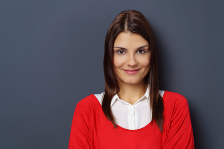 front view: Front view on single beautiful smiling woman in red sweater with copy space over dark neutral background